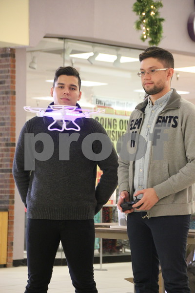The Winter Craft and Vendor Show took place at Crossroads Mall in Fort Dodge on Saturday, December 19, 2015. Pictured ( left to right) is : Virgilio Pestara, Edgardo Alture, enjoying showing the drones they had for sale. One of the larger drones is seen hovering in front of Virgilio at chin level.