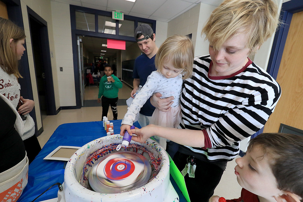 . Rachael Barton holds her daughter Norah Barton, 2, as they make some spin art during the Winter Fest at Sky View Middle School on Saturday, January 26, 2019. Rachael is also an eighth grade teacher at the school. SENTINEL & ENTERPRISE/JOHN LOVE