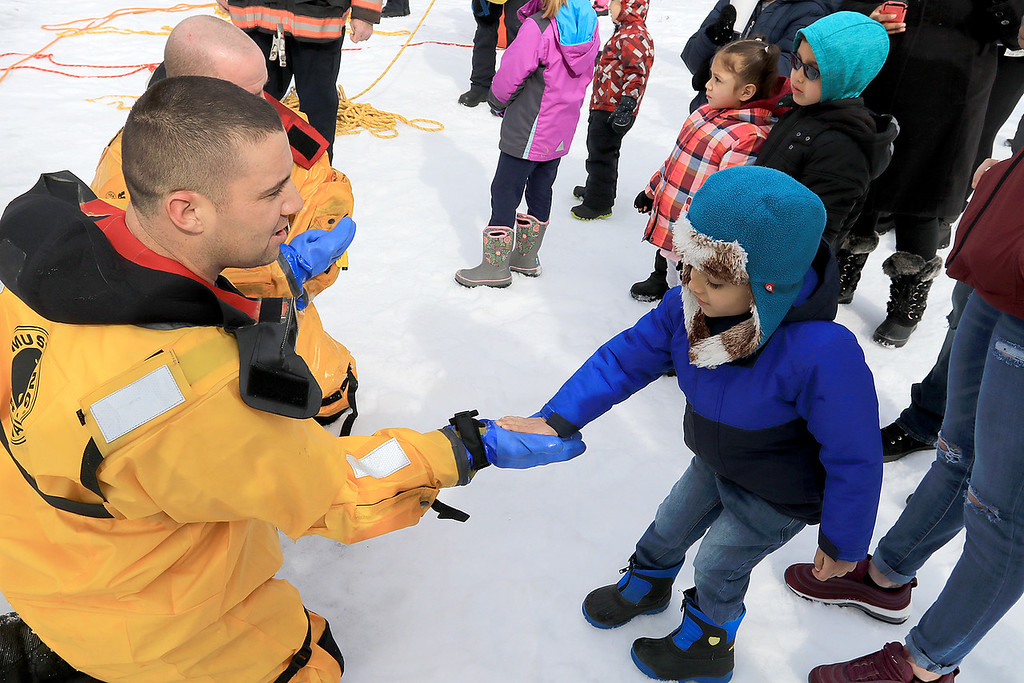 . The Leominster Recreation Department, Project Apples, Growing Places, Leominster Trail Stewards, Emergency Management, the Fire Department and the Boy Scouts joined together to offer a free winter event on Saturday, February, 23, 2019 at Barrett Park. During the event the Leominster Fire Department with Emergency Management held an ice saftey and ice rescue demonstration on Colburns Reservoir at the park. Andre Rodriguez , 4 in blue jacket, of Leominster high fives Firefighter Jon Williams after their ice rescue demonstration. With Williams is Firefighter Adam Studham. SENTINEL & ENTERPRISE/JOHN LOVE