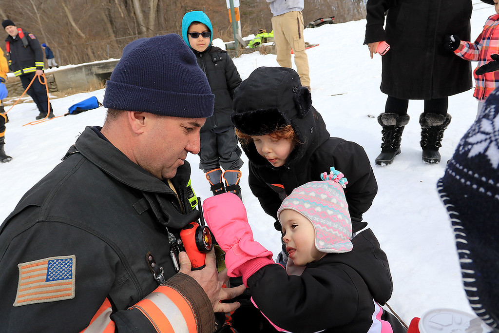 . The Leominster Recreation Department, Project Apples, Growing Places, Leominster Trail Stewards, Emergency Management, the Fire Department and the Boy Scouts joined together to offer a free winter event on Saturday, February, 23, 2019 at Barrett Park. During the event the Leominster Fire Department with Emergency Management held an ice saftey and ice rescue demonstration on Colburns Reservoir at the park. Twins Wyatt Ray and Veronica Ray, 4, of Sterling get to inspect Fire Lt. Chris Cameron\'s gear up close after their ice rescue demonstration. SENTINEL & ENTERPRISE/JOHN LOVE