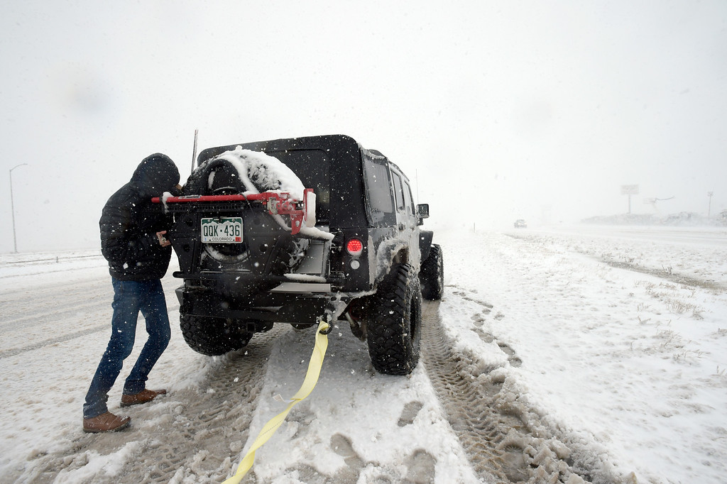 . LONGMONT, CO - MARCH 13: Tyler Elledge prepares to tow a stranded minivan off northbound I-25, near the Del Camino exit, during the blizzard March 13, 2019. To view more photos visit timescall.com. (Photo by Lewis Geyer/Staff Photographer)
