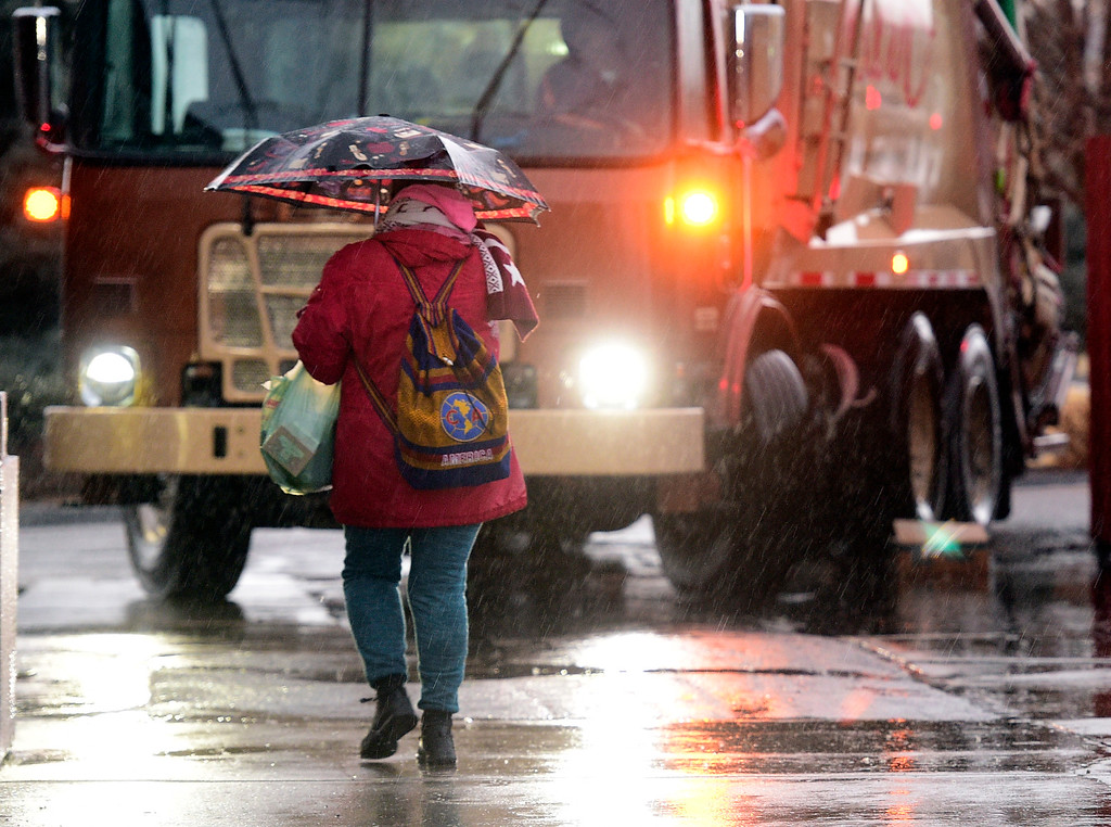 . LONGMONT, CO - March 13, 2019: A woman walks into a restaurant on N. Main in Longmont early Wednesday morning. People deal win the morning rain in Boulder County, Snow is expected by midday. For more photos, go to dailycamera.com. (Photo by Cliff Grassmick/Staff Photographer)