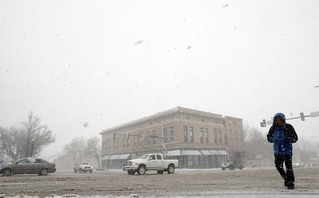 . LONGMONT, CO - MARCH 13: Randy Winkler crosses Third Avenue at Main Street during the blizzard March 13, 2019. To view more photos visit timescall.com. (Photo by Lewis Geyer/Staff Photographer)