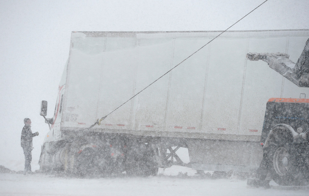 . LONGMONT, CO - MARCH 13: A tow truck driver prepares to pull a semi out of the median of northbound I-25, two miles south of Del Camino, during the blizzard March 13, 2019. To view more photos visit timescall.com. (Photo by Lewis Geyer/Staff Photographer)