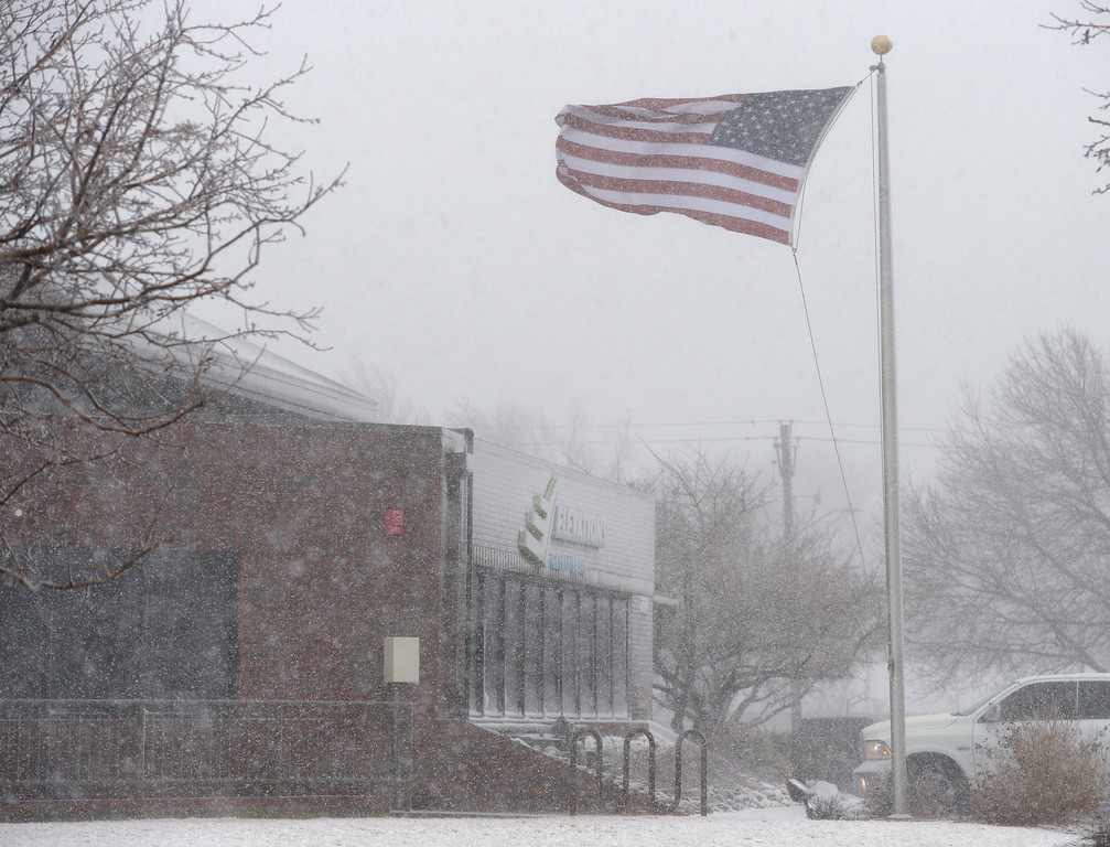 . LONGMONT, CO - MARCH 13: A flag in front of Elevations Credit Union along 21st Avenue is whipped in the wind during the blizzard March 13, 2019. To view more photos visit timescall.com. (Photo by Lewis Geyer/Staff Photographer)