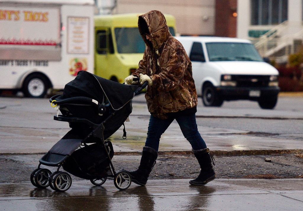 . LONGMONT, CO - March 13, 2019: A woman walks down Main Street in Longmont with a stroller early Wednesday morning.  People deal win the morning rain in Boulder County, Snow is expected by midday. For more photos, go to dailycamera.com. (Photo by Cliff Grassmick/Staff Photographer)