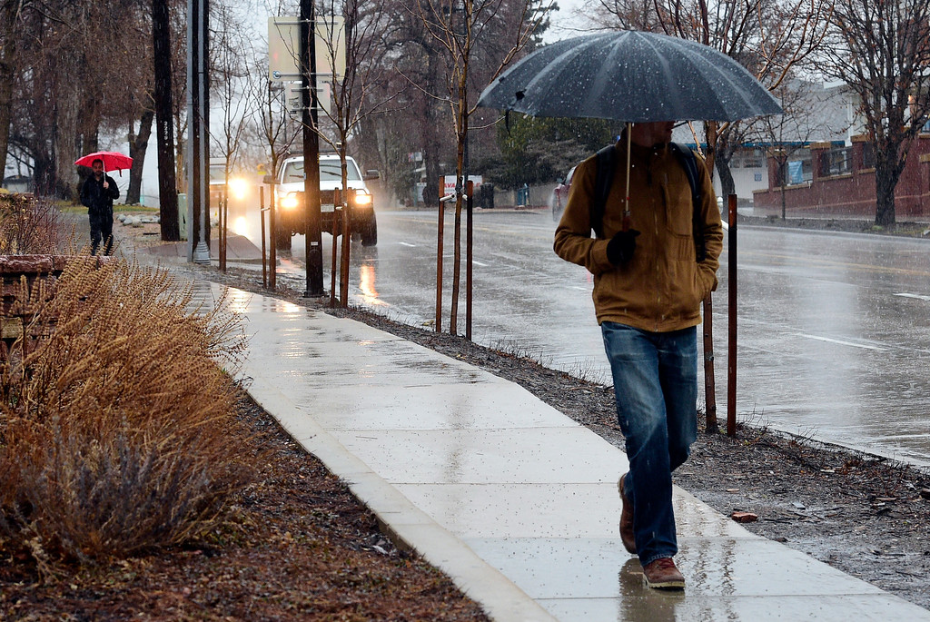 . BOULDER, CO - March 13, 2019: Two pedestrians pulled out their umbrellas for their walk down Broadway in Boulder on Wednesday. People deal win the morning rain in Boulder County, Snow is expected by midday. For more photos, go to dailycamera.com. (Photo by Cliff Grassmick/Staff Photographer)