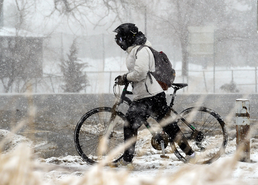 . BOULDER, CO - March 13, 2019: A person walks their bike along Baseline during a heavy snow storm in Boulder on Wednesday. For more photos, go to dailycamera.com. (Photo by Cliff Grassmick/Staff Photographer)