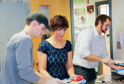 Brent Goldman, Claire Cote, and Jared Youell prepare plates for Canton Senior Center's 2016 Winter Wonderland. Goldman and Youell are related to the late Gary Youell and helped at the event in his memory.  Photo by John Fitts