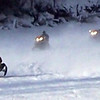 Credit: Iron Dog Volunteers<br /> <br /> Racers in the Iron Dog snowmobile race speed down a frozen river.