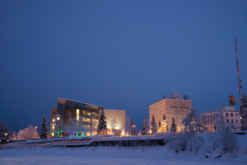 A view across the frozen Chena River of downtown Fairbanks, Alaska, and Golden Heart Plaza decorated for the holiday season.
