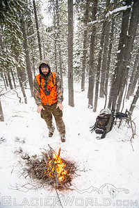 Hunter warms over a campfire in Montana