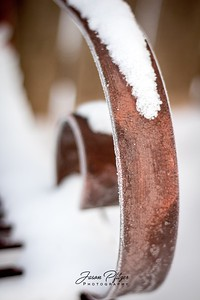 Snow and frost covered a metal bench. Love the colors of the metal. Enjoy and hold hands.
