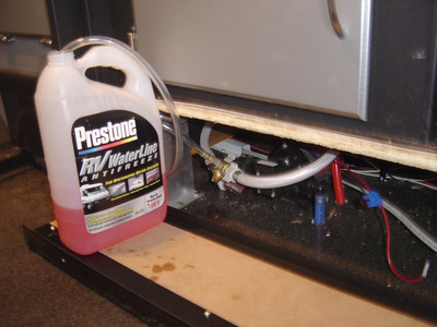 """The winterizing connection is placed  between the water line from the tank and the pump inlet.  The plastic hose from the """"T"""" is inserted into a bottle of anti-freeze."""