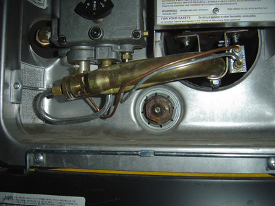 Find the large brass plug at the end of the sacrificial anode.  It is located at the bottom of your hot water heater.