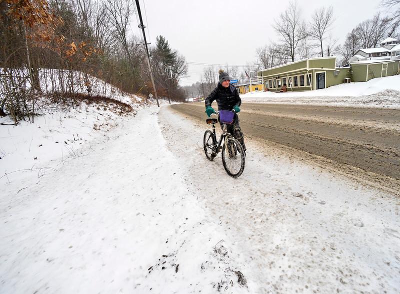 KRISTOPHER RADDER — BRATTLEBORO REFORMER<br /> Heidi Heger walks her bike up a hill on Putney Road, in Brattleboro, Vt., during a snowstorm on Thursday, Feb. 6, 2020.