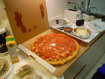 "We discovered that ""Chicago-style"" deep dish pizza is not all about the crust. Chicago style is when they add extra chunky tomato sauce on top of the pizza, to hold everything together. This whole pizza in its box weighed about ten pounds. Or maybe twenty. And yes, that IS cheesy garlic bread to the right of the pizza. With tomato sauce for dipping, of course."