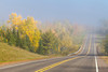 Highway 13 with fall foliage color and fog in northern Wisconsin, USA.