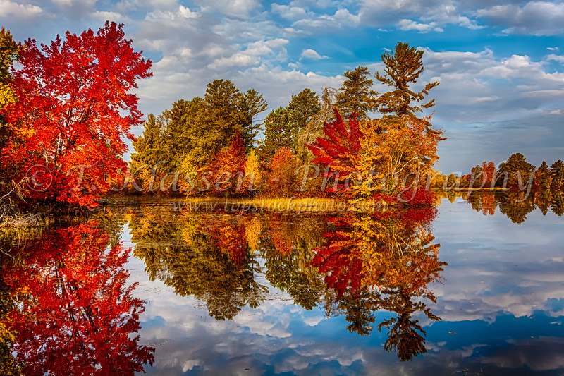 Fall foliage color in the trees reflected in a small lake near Hayward, Wisconsin, USA.