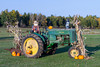 A vintage John Deere tractor decorated in fall with pumpkins and scarecrow in northern Wisconsin, USA.
