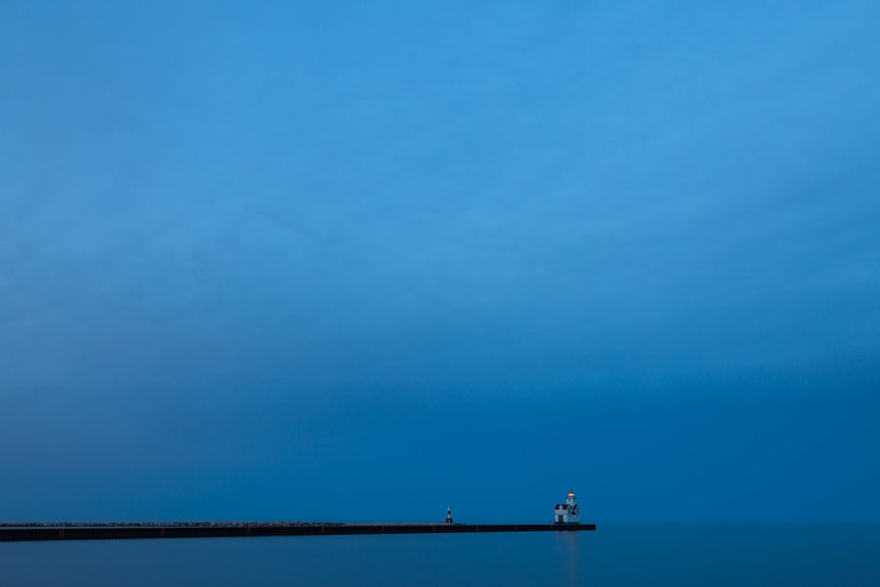 The Kewaunee Lighthouse shines its beacon under the blue sky and open waters of Lake Michigan.<br /> <br /> WI-100515-0304