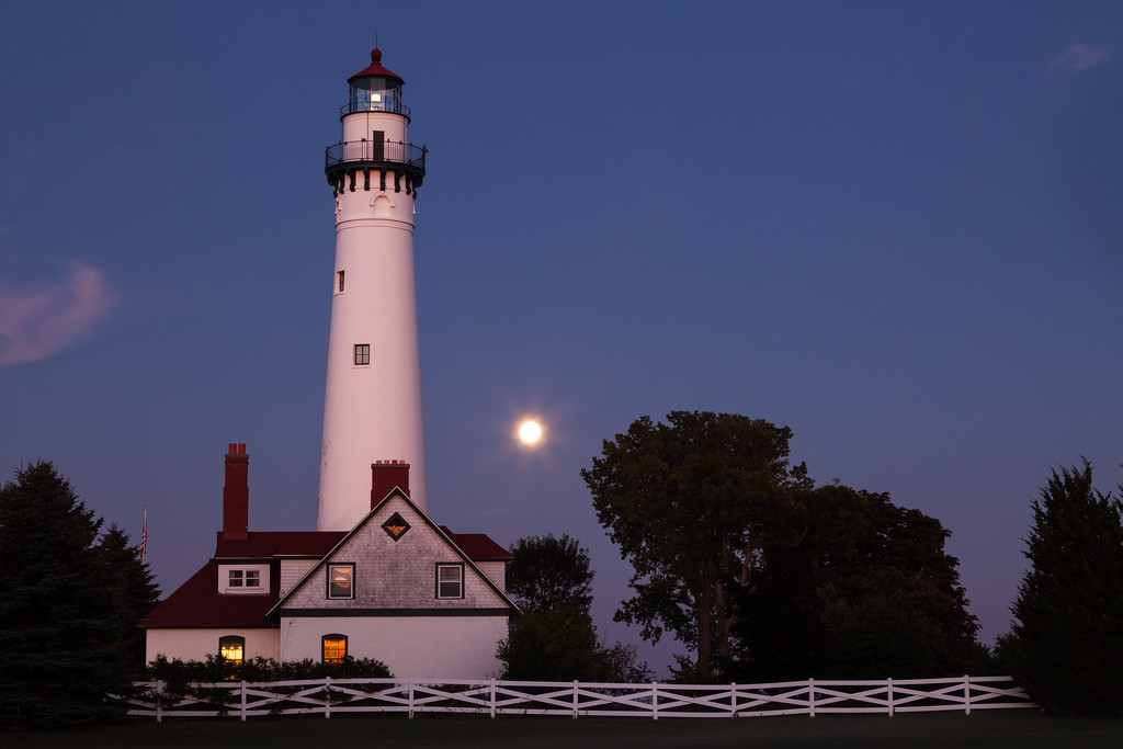 The Wind Point Lighthouse, considered by many the most beautiful lighthouse on Lake Michigan, is painted with the last light of the day. Behind it, the full moon rises. Racine, WI<br /> <br /> WI-090904-0013