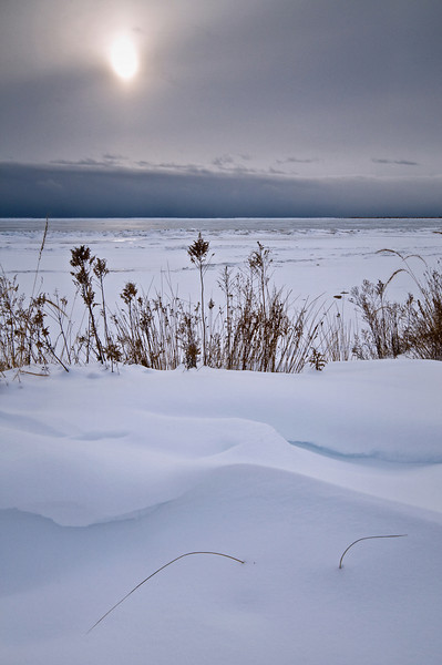 WI 084                          Pale winter sunlight illuminates the contours of drifted snow on the shore of Europe Bay, Newport State Park, Door County, WI.