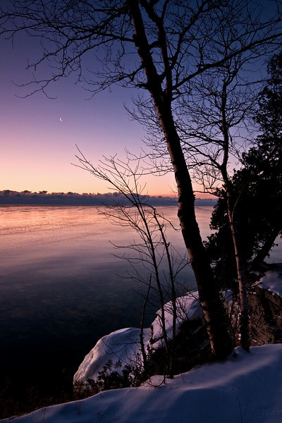 WI 079                          A crescent moon rises over a frigid Lake Michigan at dawn, Cave Point County Park, Door County, WI.