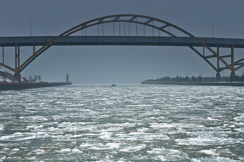 Fisherman brave the harsh elements,wind, rain, cold, fog and ice man under the Hoan bridge Milwaukee.Man must fish!