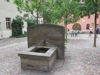 An old well in the city. The pink building in the background is the home of Cranach