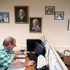 Buyer Dominick Yarnal works under a display of historic photos in the office at Wohrle's Foods in Pittsfield.<br /> Wednesday, July 28, 2021. BEN GARVER — THE BERKSHIRE EAGLE