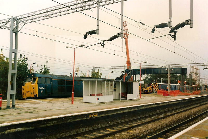The new partially erected footbridge is seen spanning platforms one and two at Wolverton on 21 October 1991. 31434 is also present on the electrification train.