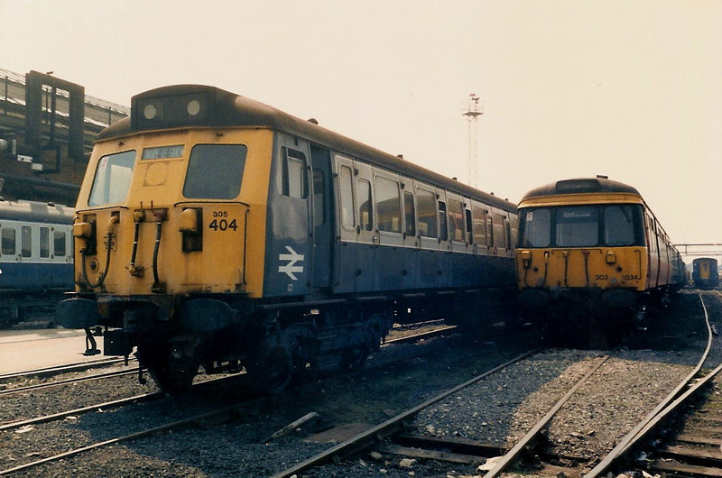 305404 stands alongside Scottish visitor 303034 in the main yard inside Wolverton Works on 17 April 1987.