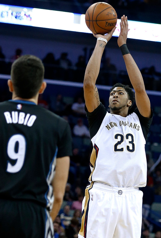. New Orleans Pelicans forward Anthony Davis (23) shoots over Minnesota Timberwolves guard Ricky Rubio during the second half of an NBA basketball game Tuesday, Jan. 19, 2016, in New Orleans. The Pelicans won 114-99. (AP Photo/Jonathan Bachman)
