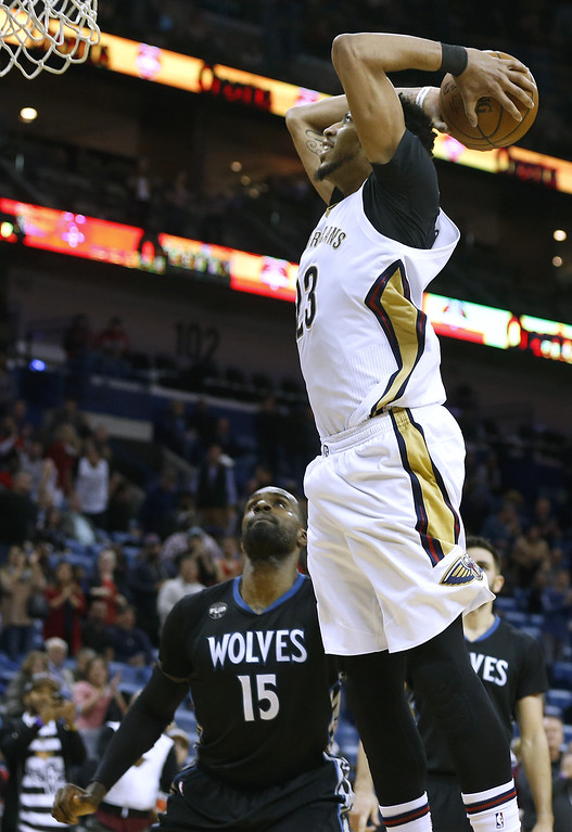 . New Orleans Pelicans forward Anthony Davis goes in for a dunk as Minnesota Timberwolves forward Shabazz Muhammad (15) watches during the second half of an NBA basketball game Tuesday, Jan. 19, 2016, in New Orleans. The Pelicans won 114-99. (AP Photo/Jonathan Bachman)