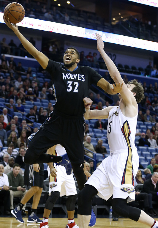 . Minnesota Timberwolves center Karl-Anthony Towns (32) drives to the basket past New Orleans Pelicans center Omer Asik during the first half of an NBA basketball game Tuesday, Jan. 19, 2016, in New Orleans. (AP Photo/Jonathan Bachman)