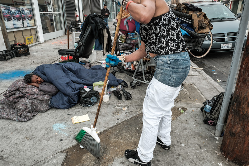 Woman sweeps as another sleeps,4th Street and Crocker Avenue