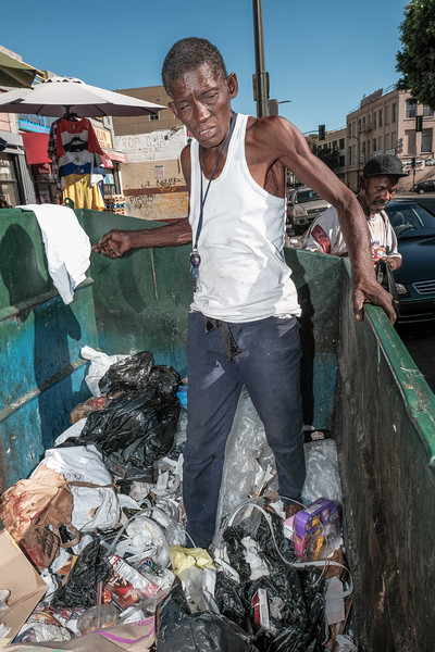Bridget searches the dumpsters on Skid Row for anything she can gather to recycle