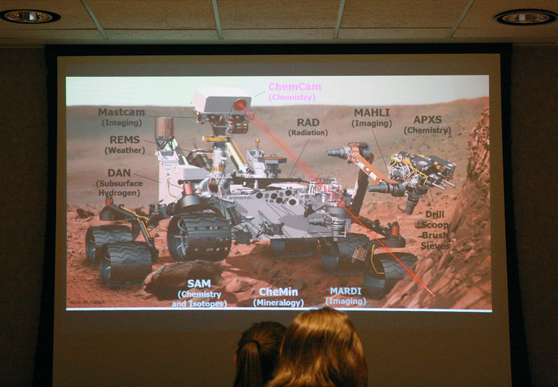 An image details the various instruments on the Curiosity Mars rover as alumna Sarah Lamm talks about her career path at the Women of K-State's Lunch and Learn event on March 28 in the Student Union. The ChemCam, labeled in purple, uses a Class 4 laser to collect data on the elemental makeup of Martian rocks. (Dene Dryden | Collegian Media Group)