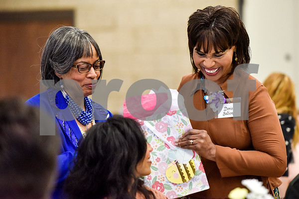 Doris Batson, right, receives a gift as she is honored during the Women in Tyler Luncheon at the Tyler Rose Garden Center in Tyler, Texas, on Thursday, March 23, 2017. The Women in Tyler Planning Committee honored six women who have made an impact in the community. (Chelsea Purgahn/Tyler Morning Telegraph)