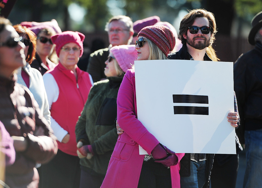 . (CHRIS RILEY �Times-Herald) A couple hold an equal sign during the Women\'s Anniversary March Napa Valley down Third Street in Napa on Saturday.