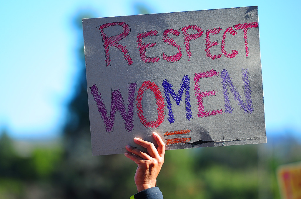 . (CHRIS RILEY �Times-Herald) A man holds up a sign during the Women\'s Anniversary March Napa Valley down Third Street in Napa on Saturday.