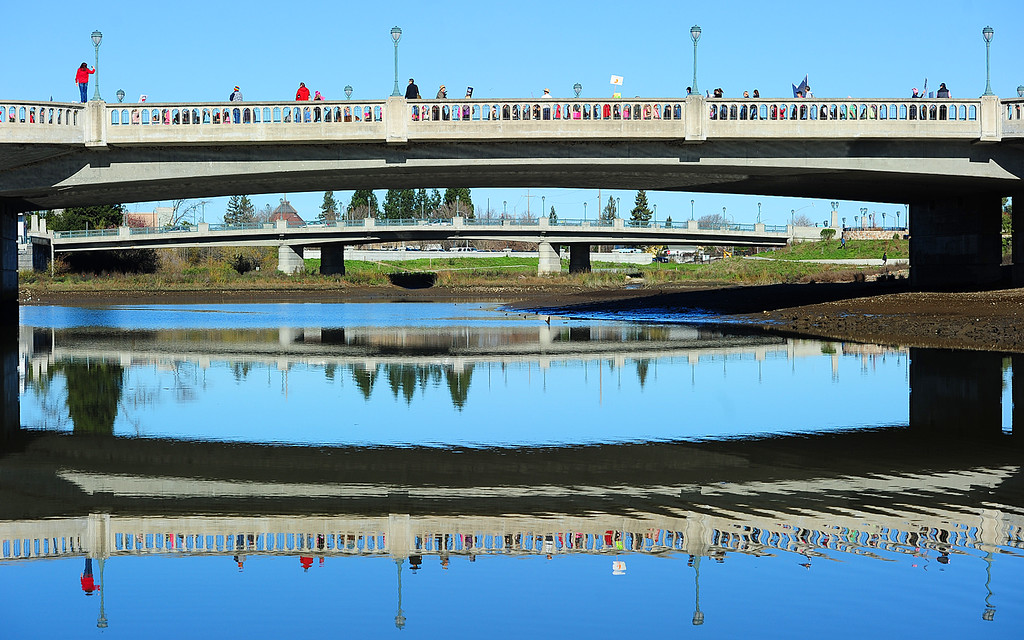 . (CHRIS RILEY �Times-Herald) Marchers are reflected in the water of the Napa River as they cross the Third Street bridge during the Napa Valley Woman\'s March on Saturday.