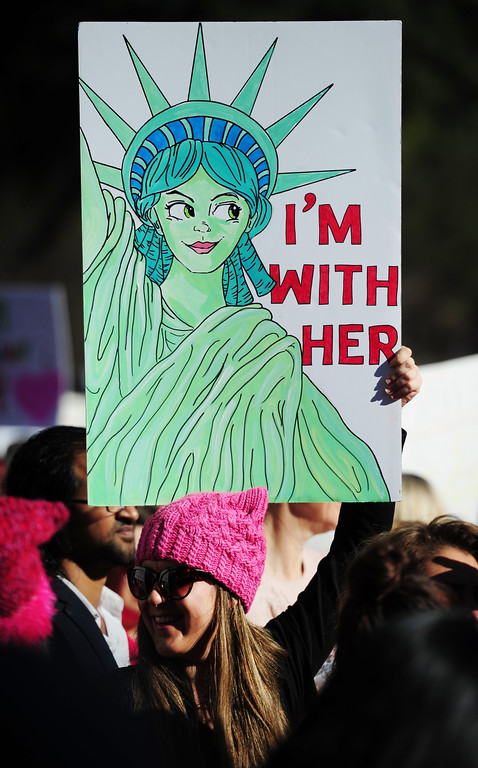 . (CHRIS RILEY �Times-Herald) Shannon Hattyar of Napa holds her artwork on a sign during the Women\'s Anniversary March Napa Valley down Third Street in Napa on Saturday.