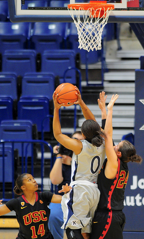 Xavier guard Tyeasha Moss (0) drives past USC Trojans guard Ashley Corral (24) (right) and USC Trojans guard Len'Nique Brown (14) for a lay up.   (#4) Xavier defeated USC Trojans 69 - 66 at the Cintas Center in Cincinnati, Ohio.