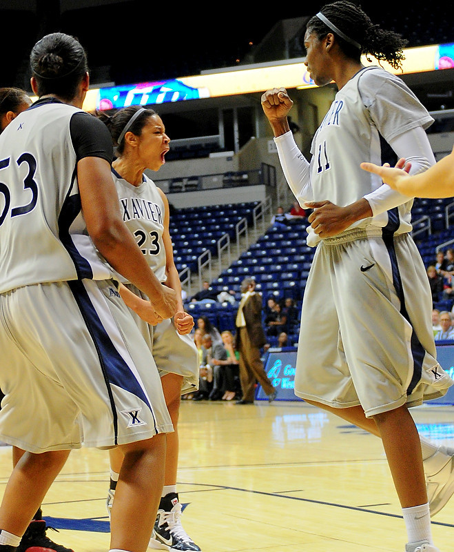 Xavier guard Megan Askew (23) gets fouled while making a lay up celebrates with teammates Xavier forward Amber Harris (11) (right) and Xavier center Ta'Shia Phillips (53).   (#4) Xavier defeated USC Trojans 69 - 66 at the Cintas Center in Cincinnati, Ohio.