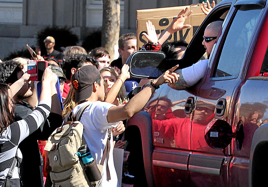 . A man who intentionally drove his Chevrolet Silverado truck around a traffic barricade to proceed toward a group of assembled protesters blocking the intersection of Pacific Avenue and Mission Street gets into a verbal confrontation with the protesters on Wednesday. No one was injured in the incident and Santa Cruz Police pursued the man after he backed away from the scene and drove up Mission Street. (Shmuel Thaler -- Santa Cruz Sentinel)