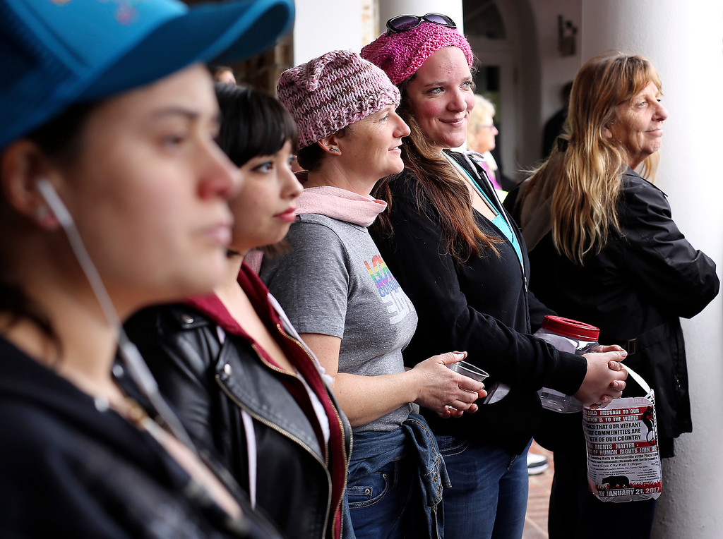. Women stand strong at Santa Cruz City Hall on Saturday before taking to Pacific Avenue during the Santa Cruz County Women\'s March. (Kevin Johnson -- Santa Cruz Sentinel)
