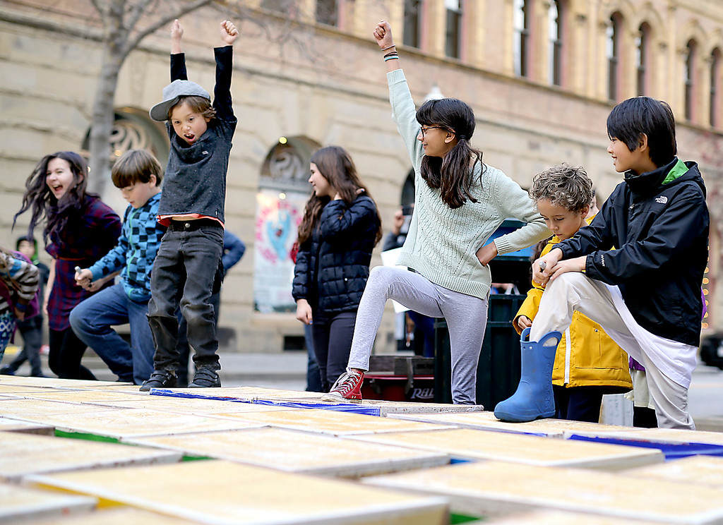 . Young children strike triumphant poses and jump on a toppled wall of cardboard boxes on Pacific Avenue in Downtown Santa Cruz on Friday during an anti-Trump protest. (Kevin Johnson -- Santa Cruz Sentinel)