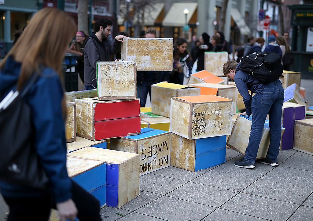 . Cardboard boxes representing bricks in Trump\'s wall lay on the ground on Pacific Avenue in Santa Cruz on Friday after being knocked down during an anti-Trump demonstration. (Kevin Johnson -- Santa Cruz Sentinel)